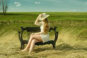 a mysterious young girl in a hat sitting on a sofa on nature