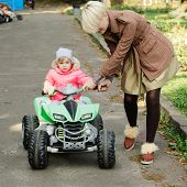 Little girl riding toy car in park