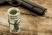 Close Up Money With Gun On Wood Background.