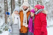 technology, season, friendship and people concept - group of smiling men and women taking selfie with smartphone and monopod in winter forest
