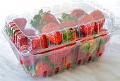 Fresh strawberries in a clear plastic box on a marble backdrop.