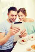 food, home, couple and technology concept - smiling couple with tablet pc reading news or taking picture and having breakfast at home