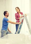 repair, renovation adn real estate concept - smiling couple hanging curtains