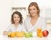 people, healthy lifestyle, family and food concept - happy mother and daughter eating healthy breakfast over home kitchen background