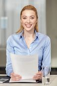 business and people concept - smiling woman holding papers in office