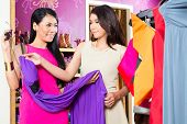 Asian young sales lady offering gown to woman in fashion store