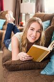 Young woman reading on the couch in her living room
