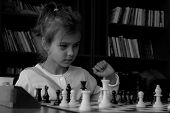 A little girl playing chess