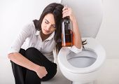 Drunk Woman In Toilet holding a whisky bottle