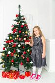 Little girl in a gray dress, standing next to tree novgodney,