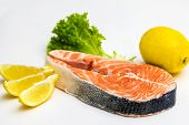 Raw Salmon Red Fish Steak With Herbs And Lemon Isolated On White