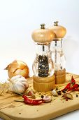Salt And Pepper Mill With Ingredients Around On Wooden Cutting Board On A White Background