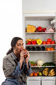 hungry woman eats meat sitting in the fridge