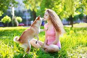 Dog And Owner Girl Outdoors In Sunny Park