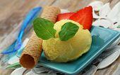 Mango sorbet garnished with mint leaf, and wafer