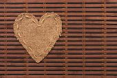 The Symbolic Heart Of Burlap Lies On A Bamboo Mat