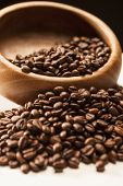 Closeup Image Of Wodden Bowl With Roasted Coffee Beans Over Black Background