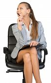 Businesswoman sitting on office chair with clipboard and pen