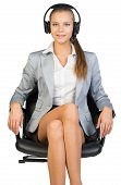 Businesswoman in headset sitting on office chair
