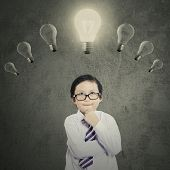 stock photo of lightbulb  - Portrait of cute little boy with thinking style while looking at the bright lightbulb - JPG
