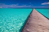 Wooden long jetty over lagoon in Maldives with amazing clean water