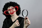 Funny Women Wearing A Black Wig And Red Heart Eyeglasses Looking Through A Magnifying Glass