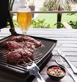 Raw beef with spices, pepper and garlic fried on an electric grill