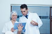 Male and female dentists using digital tablet