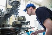 stock photo of mechanical engineering  - Engineering student using large drill at the university - JPG