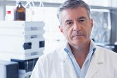 foto of scientist  - Portrait of an unsmiling scientist wearing lab coat in laboratory - JPG