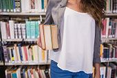 Pretty student holding books in library at the university
