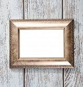 Golden photo frame on color wooden background
