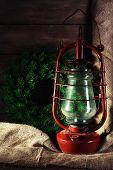 Kerosene lamp with wreath on wooden planks background