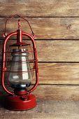 Kerosene lamp on wooden planks background