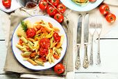 Pasta salad with pepper, carrot and tomatoes on wooden table background