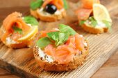 Canapes with salmon, black olive and herbs on cutting board, on wooden background