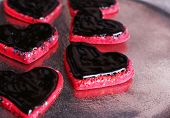 Cookies in form of heart covered chocolate on metal tray background