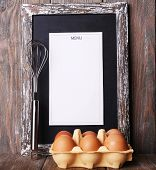 Menu board with eggs on rustic wooden planks background