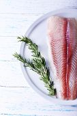 picture of pangasius  - Pangasius fillet with sprigs of rosemary on plate and color wooden table background - JPG