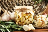 Canned garlic in glass jar and wicker mat and rosemary branches, on wooden background