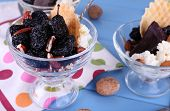 Dessert with prunes in glass bowls on color wooden planks background