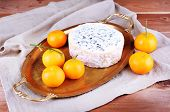 Blue cheese with oranges on metal tray on burlap cloth and wooden table background