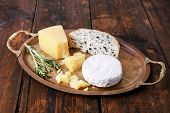Different types of cheese on metal tray and wooden table background