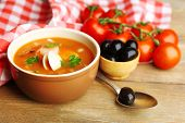 Tasty soup with shrimps, mussels, tomatoes and black olives in bowl on wooden background