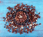 Coffee beans in black ceramic cup on blue wooden background