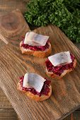 Herring with beets on rye toasts on wooden background
