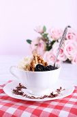 Dessert with prunes in cup with bouquet of roses on color wooden table and light background