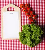 Cutting board with menu sheet of paper, with cherry tomatoes and lettuce on squared fabric background