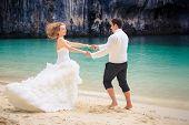 stock photo of twist  - handsome groom twist his blonde bride in elegant wedding dress near cliff on island beach Thailand - JPG
