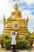 stock photo of woman dragon  - Young woman praying and meditating Gold Buddha near Thailand Phuket - JPG